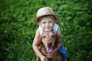 boy hugging dog with green